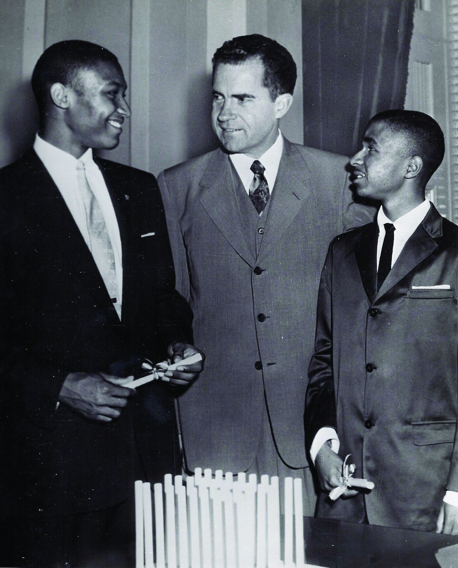Congratulations from the President: Charles Bush (left) receives his high shcool graduation from the Page School. The diploma was signed by Dwight D. Eisenhower and presented by Richard Nixon (middle).